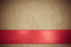 Red ribbon on brown fabric background with copy space. Stock Images