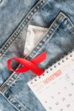 Red ribbon, calendar and condom on jeans. World AIDS Day. Red ribbon calendar and condom on jeans. World AIDS Day royalty free stock photo