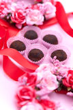 Red ribbon and chocolate truffles Stock Photo