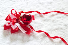 Red ribbon and Christmas ball on snow background Royalty Free Stock Photo