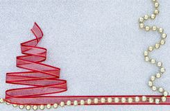Red ribbon Christmas tree with shiny golden beads on silver glitter texture background Royalty Free Stock Photos