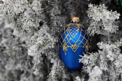 Red ribbon on the Christmas tree with snow. Blue cone on the Christmas tree with snow stock image