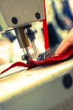 Red Ribbon and Cloth Stitched on Sewing Machine Royalty Free Stock Image