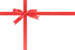 Red ribbon cross with bow for packaging with tails Royalty Free Stock Photography