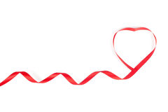Red ribbon curled in heart shape Stock Photos