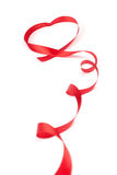 Red ribbon curled in heart shape Royalty Free Stock Images