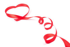 Red ribbon curled in heart shape Stock Images