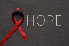 Red ribbon for the fight against AIDS Stock Images