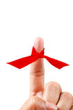 Red ribbon on finger. Red ribbon on finger isolated on white background, Save clipping path Royalty Free Stock Image