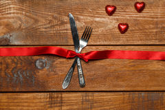 The red ribbon, fork and knife on wooden royalty free stock photo
