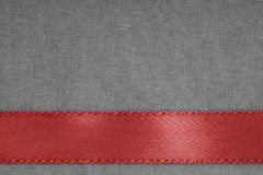 Red ribbon on gray fabric background with copy space. Royalty Free Stock Image
