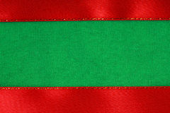 Red ribbon on green fabric background with copy space. Stock Photography