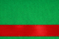 Red ribbon on green fabric background with copy space. Stock Photo
