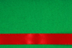 Red ribbon on green fabric background with copy space. Royalty Free Stock Photo