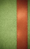 Red ribbon on green fabric background with copy space. Stock Image