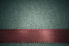 Red ribbon on green fabric background with copy space. Royalty Free Stock Photography