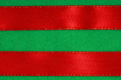 Red ribbon on green fabric background Royalty Free Stock Photos