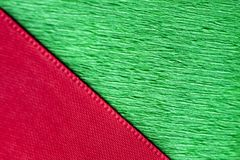 Red ribbon and green wrapping paper texture close up. Royalty Free Stock Photo