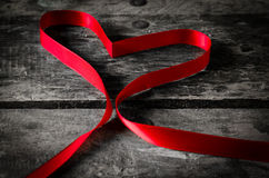 Red ribbon heart on black wooden background, Valentines Day back Royalty Free Stock Photo
