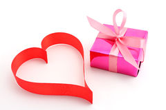 Red ribbon heart with gift wrapped present Stock Image