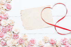 Red ribbon heart symbol with old blank paper sheet and pink rose Stock Image