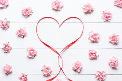 Red ribbon heart symbol with pink roses on white wooden table Royalty Free Stock Photos