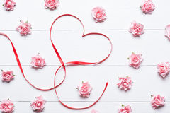 Red ribbon heart symbol with pink roses on white wooden table Royalty Free Stock Image