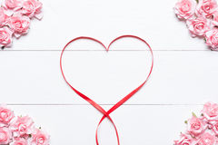 Red ribbon heart symbol with pink roses on white wooden table Royalty Free Stock Photo