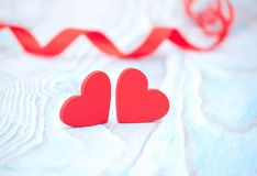 Red ribbon heart and two hearts on blue wooden background on valentine day. Stock Image
