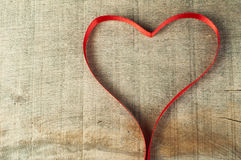Red ribbon heart on wooden background Royalty Free Stock Photos