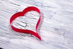Red ribbon heart on wooden background. Valentines day concept Stock Photography