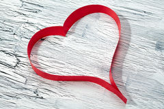 Red ribbon heart on wooden background Stock Photos