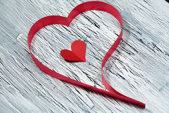 Red ribbon heart on wooden background Stock Images