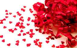 Red Ribbon and Hearts. Red curled ribbon and small red confetti hearts on white background stock photography
