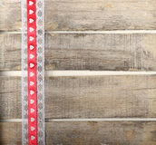 Red ribbon of hearts on old wooden background. With lace Royalty Free Stock Images