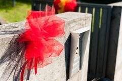 Traditional graduation party red bow outside student home as per the italian tradition. Red ribbon on house entrance as per Italian graduation tradition Stock Photo