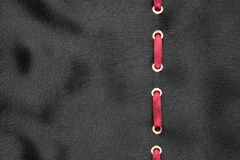 Red ribbon are inserted in a black wavy satin. Fashionable beautiful background. Stock Photography