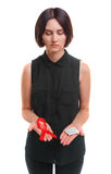 A girl holding a condom and a red ribbon isolated on a white background. Medical support. Safe sex propaganda concept. A red ribbon and a packed condom in hands Stock Photography