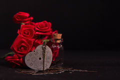 Red ribbon rose, glass bottle and heart clock with black background Royalty Free Stock Photos