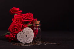 Red ribbon rose, glass bottle and timeless heart clock with black background Royalty Free Stock Image