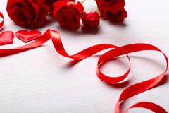 Red ribbon with roses and hearts on table Royalty Free Stock Images