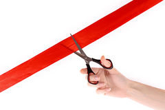 Red ribbon, scissors and hand isolated Royalty Free Stock Photo