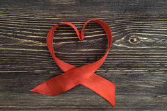 A red ribbon shaping heart ,  on wooden background Royalty Free Stock Photography