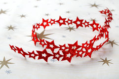 Red ribbon of stars on christmas cloth Royalty Free Stock Photo