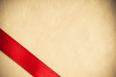 Red ribbon stripe on bright cloth background. Stock Photos