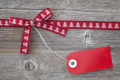 Red ribbon with a tag. On wooden background Stock Images