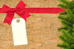 Red ribbon with a tag and christmas tree branch on wooden backgr Royalty Free Stock Photo