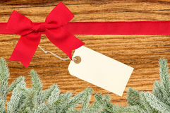 Red ribbon with a tag and christmas tree branch on wooden backgr Stock Photos