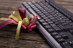 Red ribbon on top of wooden near black Keyboard - very shallow depth of field. Stock Photo