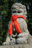 A red ribbon was knotted around the statue of a lion installed in the courtyard of a buddhist temple in Hoi An (Vietnam) Stock Photos
